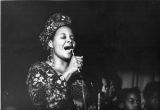 Woman in a head wrap singing into microphone, 1973
