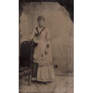 An African-American woman leaning on chaise lounge.