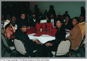 Attendees seated at Christmas Kwanzaa soiree Christmas/Kwanzaa Soiree