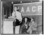 [Roy Wilkins standing at lectern during the NAACP 34th Annual Conference, Detroit, Michigan - Walter F. White and another man are seated behind Wilkins]