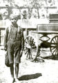 African American boy in front of wagon, portrait