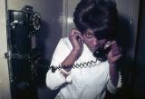 Lela Ballard talking on a pay telephone at the Laicos Club in Montgomery, Alabama.