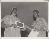 Jitu Weusi receiving a certificate from Mensah Wali