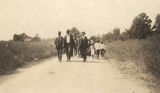 Members of an African American congregation walking down a dirt road from the church building to a creek for a baptism.