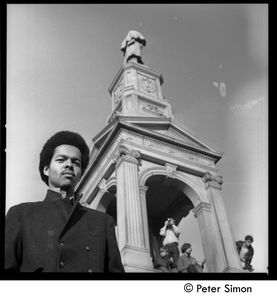 Unidentified African American man standing by the Civil War memorial in Cambridge Common, antiwar protesters clambering over the memorial