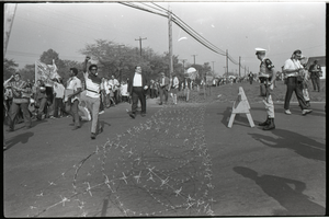 Antiwar demonstration at Fort Dix, N.J.: line of protesters marching past barbed wire and military police barricade (one raising fist in Black Power salute)