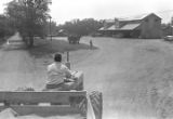 Man driving a tractor down a dirt road toward a cotton gin near Mount Meigs in Montgomery County, Alabama.