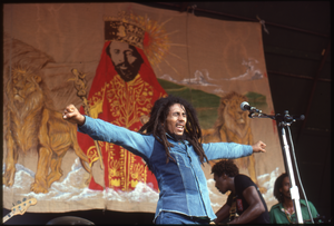 Bob Marley on stage, with arms outstretched in front of a painting of Haile Selassie