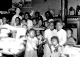 Children and a woman posing for a picture in a school room