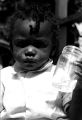 Small child holding a glass jar on the porch of a house in Newtown, a neighborhood in Montgomery, Alabama.