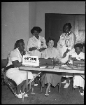 """Five women at table with sign, """"registration courtesy of San Diego City and County Convention Bureau"""""""