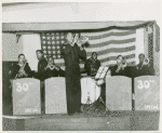 Group portrait of African Americans, Seabee Band members, from the 30th Special U.S. Naval Construction Battalion, playing on a stage