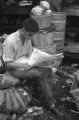 Jasper Wood Collection: Young man reading newspaper at produce stand