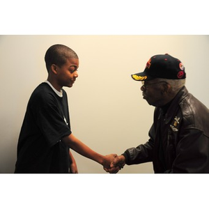 Willis D. Saunders Jr. shakes hands with a young African-American boy.