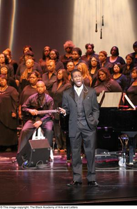 A Singer stands Center Stage In Front of Ensemble Black Music and the Civil Rights Movement Concert