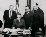 Robert C. Weaver (far right), New York State Rent Administrator, and others looking on as New York State Governor W. Averell Harriman signs documents