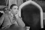 Joseph Lowery sitting behind the podium, listening to Martin Luther King, Jr., speak during a meeting at St. Paul AME Church in Birmingham, Alabama.