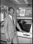 African American automobile dealer posing near a car, Los Angeles, 1983