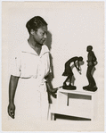 """Augusta Savage with two of her statuettes, entitled (left to right) """"Susie Q"""" and Truckin'"""""""