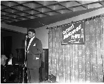 """Man speaking at microphone in front of """"Calvert welcomes ILWU and guests"""" banner"""