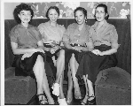 Four waitresses, all similarly dressed, seated in restaurant dining booth, Slim Jenkins nightclub Oakland, California