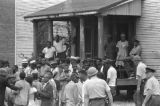 Crowd of African Americans in front of a house, looking toward the scene of the 16th Street Baptist Church bombing.