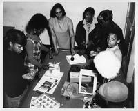 A group of African Americans work at a table of Christmas ornamentation.