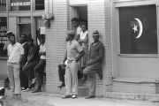 African Americans in front of a brick building, looking toward the scene of the 16th Street Baptist Church bombing.