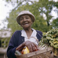 Hattie Dillard holding a basket of vegetables at her produce stand, probably in Birmingham, Alabama.