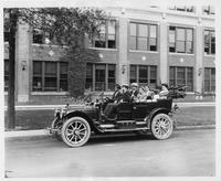 1910 Packard 30 Model UC, parked on street in front of Packard plant, with family of six and chauffeur