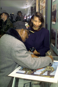 "A former member of the 555th Parachute Infantry Battalion, ""Triple Nickels,"" signs a poster, at the 82nd Airborne Division museum, that commemorates his unit. The 555th is recognized as the first African-American unit to be integrated into the Army. It joined the 3rd Brigade, 82nd Airborne Division in December 1947"