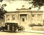 Carnegie building with the Greensboro Public Library's first bookmobile parked in front
