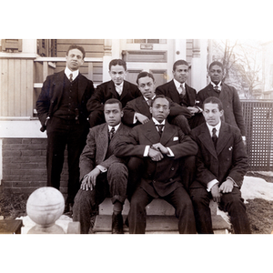 Eight men gather for a group photograph