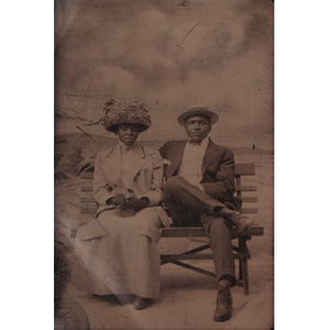 An African-American couple sitting on a bench.