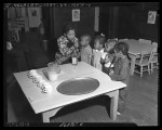 African American woman feeding cod liver oil to four African American children at a Macy Street school, circa 1938