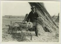 """Unknown African American male with a hand brake in a field of hemp stalk stacks at at a Castleton Farm, Lexington, Kentucky; used as illustration facing page 35 in Coleman's """"Slavery times in Kentucky"""" with caption: """"OLD SLAVE WITH HAND HEMP-BRAKE"""", 1940"""