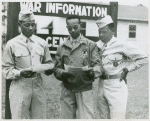 African American officer candidate Perry Johnson (left) and Corporal George Bethel (center) standing and reading papers while African American officer candidate Travis L. Banks (right) looks on, Fort Benning, Georgia