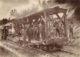 Group standing on a train car in front of an engine.
