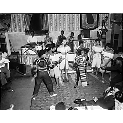 Mariachi performance with female vocalist and adolescents in costume, possibly including a young George Benson, performing with a six-piece jazz band in a club with ocean liner banners