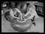 Manpower. Negro bomber plant workers. Conservation of rubber by American motorists makes possible these bomber tires, which are being assembled in a large Eastern aircraft plant. These Negro workers are clamping on lock washers to the wheels before final assembly of the landing gear. Glenn L. Martin Bomber Plant. Baltimore, Maryland