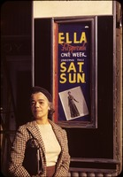 Peterson, Dorothy Randolph, in front of a poster for Ella Fitzgerald at the Savoy Ballroom, Harlem, New York City
