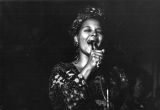 Woman in head scarf sings into microphone, 1973