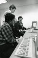 A College of Business Administration faculty member instructs two students in the computer lab