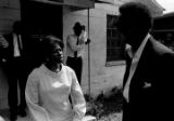 Barbara Howard Flowers, staff member at the Southern Courier, speaking with Stokely Carmichael while standing in the yard in front of the Autauga County Improvement Association office in Prattville, Alabama.