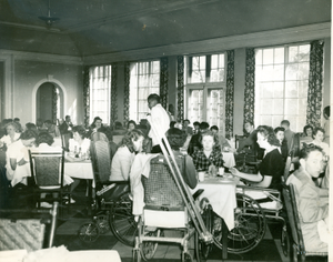 Photograph of a group of Georgia Warm Springs Foundation patients and staff eating a meal in the Georgia Hall dining room at the Georgia Warm Springs Foundation, Warm Springs, Meriwether County, Georgia, 1937-1947?