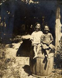 2 children of African descent, sitting on a barrel, mouths open