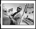 Man holding up a copy of Final call at a street corner, Los Angeles, 1996