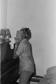 Josephine Bradford dusting a piano at her parents' home in Montgomery, Alabama.
