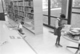 Little boy and girl looking at magazines and books on a table at the Montgomery Public Library.
