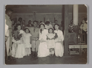 Photographic print of a sergeant and bride surrounded by wedding guests